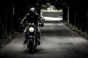 Motorradfahrer auf einer Allee